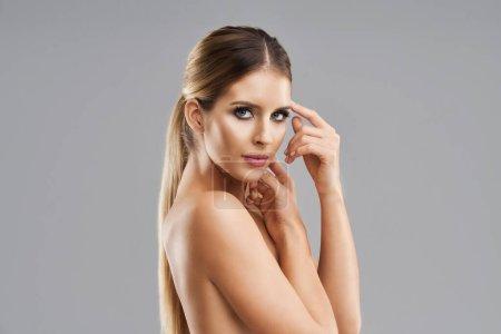 Photo pour Blond belle femme adulte posant sur fond gris - image libre de droit