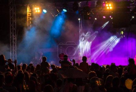 Photo pour Foule de concert assister à un concert, des silhouettes de gens sont visibles, rétro-éclairé par les lumières de la scène. Mains surélevées et les téléphones intelligents sont visibles ici et là. - image libre de droit