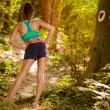Beautiful sporty woman practicing yoga in the forr...