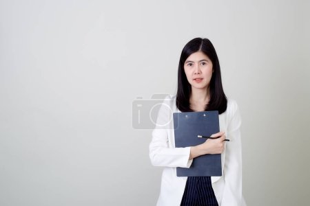 Photo for Portrait of a attractive asian businesswoman holding pencil and clipboard gray background Technology concepts and education - Royalty Free Image