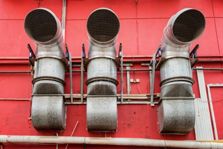 ventilation pipes outside a red building