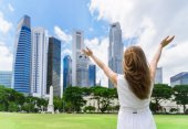 Young woman with raised arms at lawn on skyscrapers background