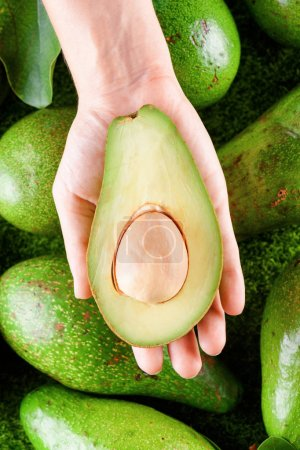Hand holding half of fresh ripe avocado. Healthy eco food