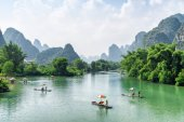 View of tourist bamboo rafts sailing along the Yulong River