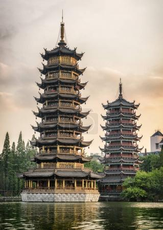 Photo for The Sun and Moon Twin Pagodas at Shanhu Lake (Fir Lake) in downtown of Guilin in China at sunset. Guilin is a popular tourist destination of Asia. - Royalty Free Image