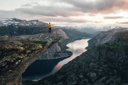 Photo for Breathtaking view of Trolltunga rock - most spectacular and famous scenic cliff in Norway. Picturesque landscape with sunset sky and clear lake - Royalty Free Image