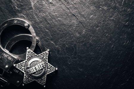 Photo pour Étoile de shérif et les menottes sur table ardoise noire agrandi. Fond de notion de droit - image libre de droit
