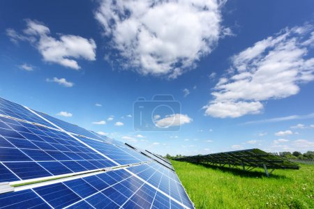 Foto de Solar panel on blue sky background. Green grass and cloudy sky. Alternative energy concept - Imagen libre de derechos