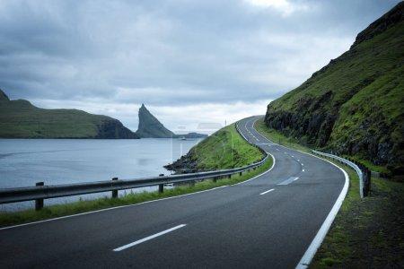 Photo pour Vue spectaculaire du soir sur la route et les rochers Drangarnir et Tindholmur en arrière-plan sur l'île de Vagar, îles Féroé, Danemark - image libre de droit