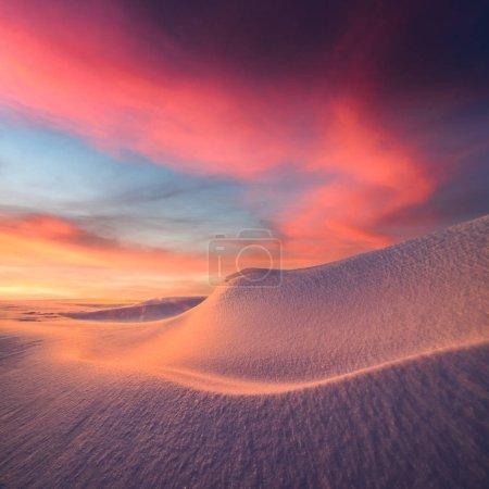 Photo pour Paysage hivernal fantastique dans les montagnes enneigées rayonnant par la lumière du soleil du soir. Scène hivernale dramatique avec collines enneigées gelées au coucher du soleil. Noël fond de vacances - image libre de droit