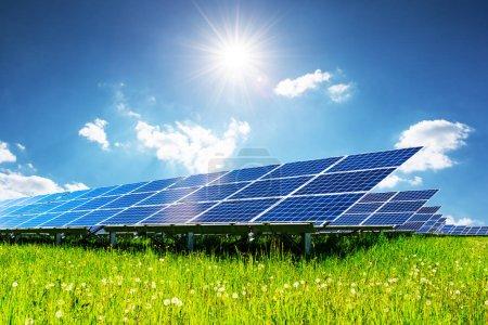 Foto de Panel solar bajo cielo azul con sol. Hierba verde y cielo nublado. El concepto de energía alternativa - Imagen libre de derechos