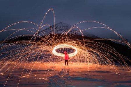 Photo pour Spectacle de feu avec beaucoup d'étincelles dans les montagnes d'hiver de nuit. Photographie de paysage - image libre de droit