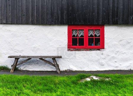 Photo pour Mur de la maison blanche avec fenêtre rouge sur la vieille maison faroese. Banc en bois sur herbe verte. Îles Féroé, Danemark - image libre de droit