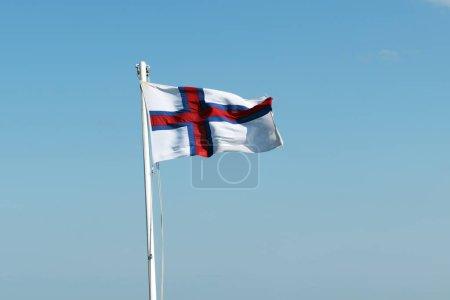 Photo pour Drapeau des îles Féroé agitant contre un ciel bleu clair - image libre de droit