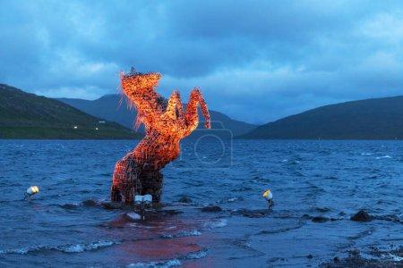Photo pour Incroyable scène du soir avec un cheval mythique lumineux Nykur Nix Statue dans les eaux du lac Sorvagsvatn près de l'aéroport de Vagar sur les îles Féroé, Danemark - image libre de droit