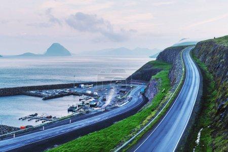 Photo pour Vue imprenable sur une jetée avec des voitures et des bateaux près du village Velbastadur sur l'île Streymoy, îles Féroé, Danemark. Photographie de paysage - image libre de droit