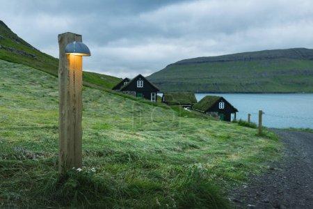 Photo pour Vue pittoresque sur les maisons traditionnelles faroese couvertes d'herbe dans le village Bour à l'heure du soir. Île de Vagar, Îles Féroé, Danemark . - image libre de droit