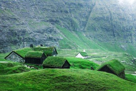 Photo pour Vue d'été de l'église traditionnelle Saksunar Kirkja sur gazon dans le village de Saksun. Paysage de beauté avec des maisons herbeuses et de hautes montagnes. Streymoy île, Îles Féroé, Danemark . - image libre de droit