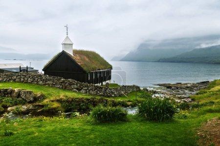 Photo pour Vue d'été de l'église traditionnelle en gazon dans le village faroese. Paysage de beauté avec fjord brumeux et hautes montagnes. Streymoy île, Îles Féroé, Danemark . - image libre de droit