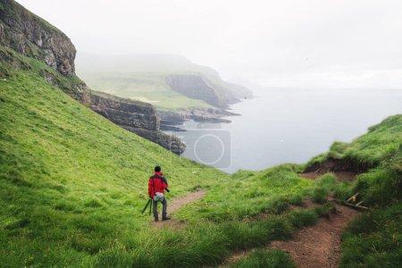 Photo pour Vue dégagée sur l'île de Mykines avec un touriste en veste rouge sur les îles Féroé, Danemark. Photographie de paysage - image libre de droit