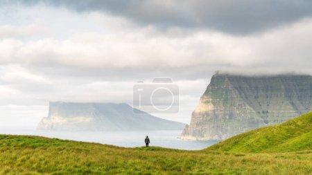 Photo pour Un touriste solitaire près d'un petit lac regarde les îles brumeuses de l'océan Atlantique depuis l'île de Kalsoy, îles Féroé, Danemark. Photographie de paysage - image libre de droit