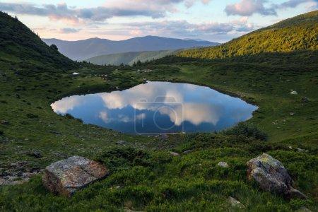 Majestatyczny wiosenny, słoneczny poranek. Krajobraz górski z jeziorem. Piękna chmura odbija się w wodzie. Lokalizacja Karpaty, Ukraina, Europa.