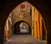 The picturesque  medieval street of Ferrara with arcs