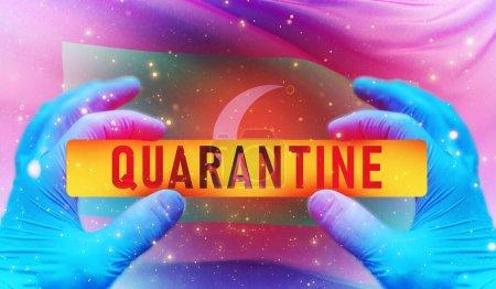 Photo for Medical hand with lettering QUARANTINE, Coronavirus quarantine area sign on flag of Maldives - Royalty Free Image