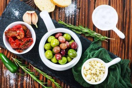 olives, cheese and dry tomatoes on wooden table