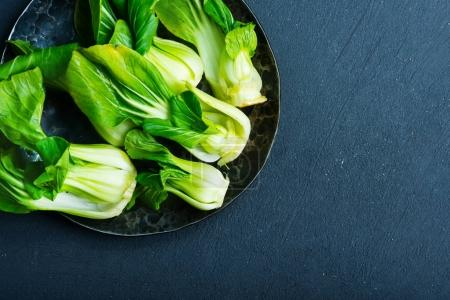 Fresh pak choi on plate  on a table...