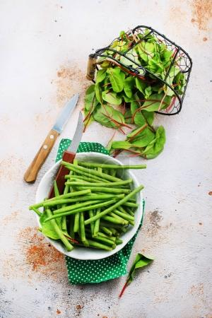 Photo for Green beans in bowl and fresh leaves of mangold on table - Royalty Free Image