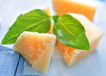 Parmesan cheese pieces and basil leaves