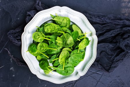 Photo for Fresh green spinach leaves on plate, baby spinach, healthy diet concept - Royalty Free Image