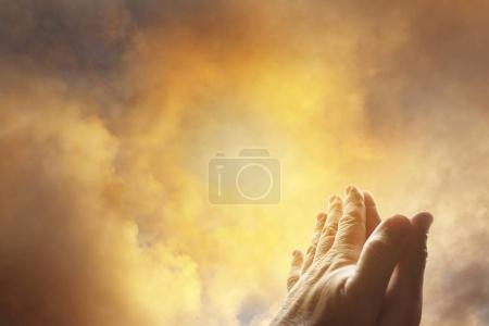 Photo pour Mains priant ensemble dans le ciel lumineux - image libre de droit
