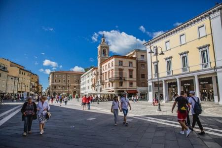 Historical architecture and people on street of Rimini city, Italy