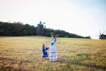 Young mother and her daughter in ukrainian national dresses walking outdoors