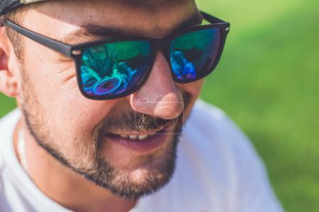Close-up portrait of young handsome man in stylish sunglasses