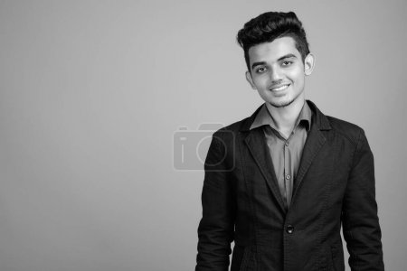 Photo for Studio shot of young Indian businessman in suit against gray background in black and white - Royalty Free Image