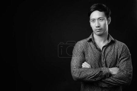 Photo pour Studio shot de jeune homme d'affaires asiatique beau sur fond noir en noir et blanc - image libre de droit