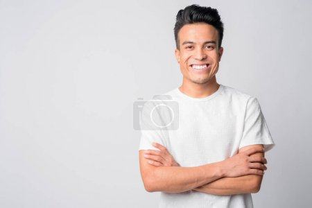 Photo for Studio shot of young Asian man against white background - Royalty Free Image
