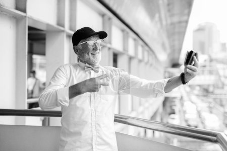 Photo pour Portrait of handsome bearded senior tourist man wearing stylish clothes while exploring the city of Bangkok in black and white - image libre de droit