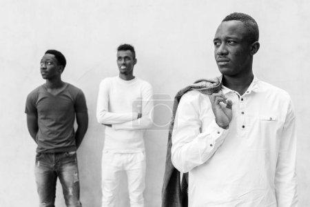 Photo pour Portrait de trois jeunes Africains pendus contre un mur de béton à l'extérieur en noir et blanc - image libre de droit