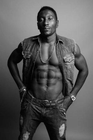 Photo pour Photo prise au studio d'un jeune et beau Africain sur fond gris en noir et blanc - image libre de droit