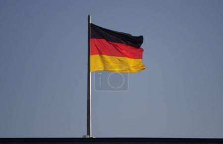 Photo pour Brandissant le drapeau de l'Allemagne contre le ciel bleu - image libre de droit