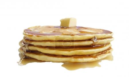Homemade pancakes with butter and maple syrup on w...