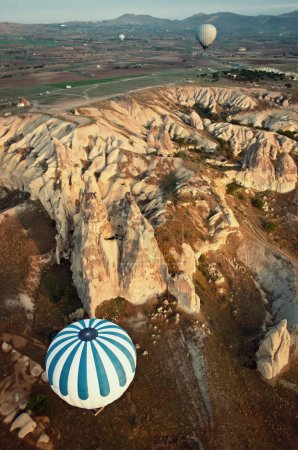 Hot air balloons over mountain landscape in Cappadocia