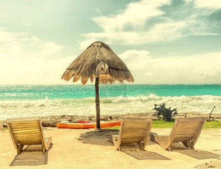 sunny tropical beach with chairs and umbrella