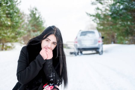 Portrait of a beautiful young girl, whose car broke down in the winter forest