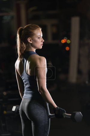 Photo for Beautiful sporty woman doing power fitness exercise at sport gym. Girl with dumbbell on black. - Royalty Free Image