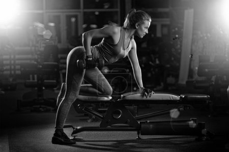 Photo for Beautiful sporty woman doing power fitness exercise at sport gym. Girl with dumbbell black and white. - Royalty Free Image